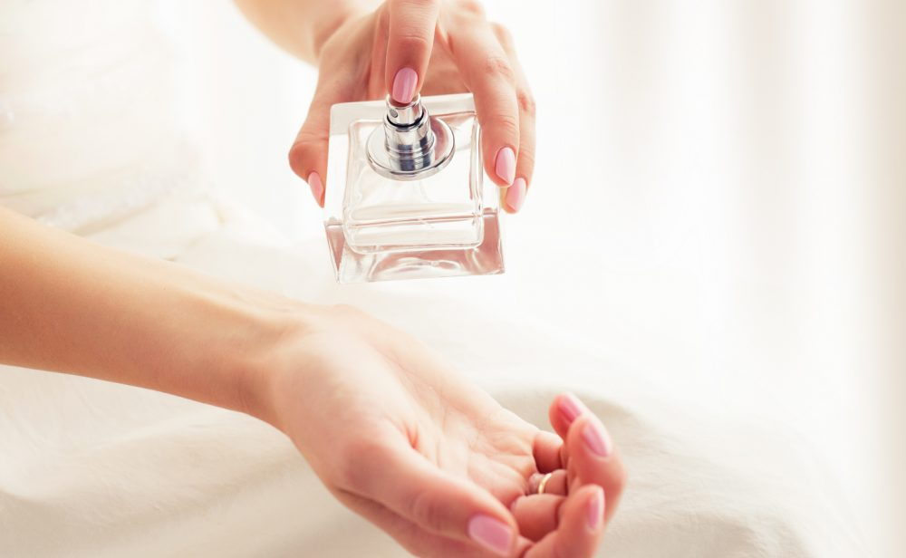 woman with pink nails spraying perfume on her wrist