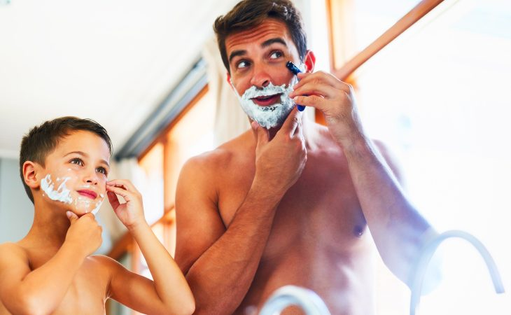 Father teaching son how to shave with shaving cream on faces.