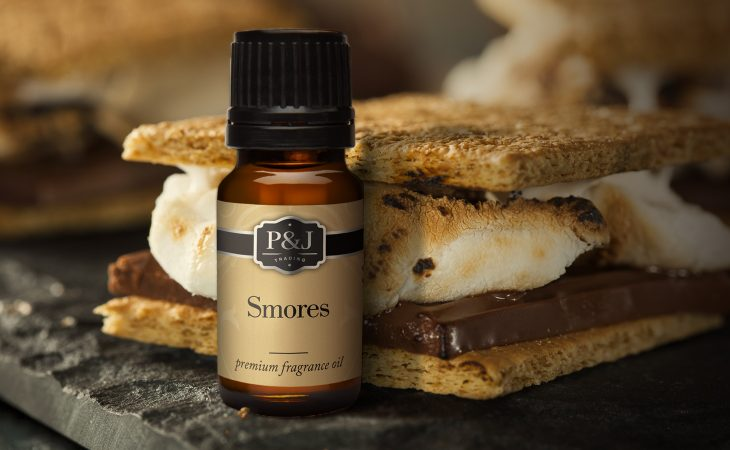 A bottle of P&J Trading Smores premium fragrance oil, placed right next to a delicious smore.