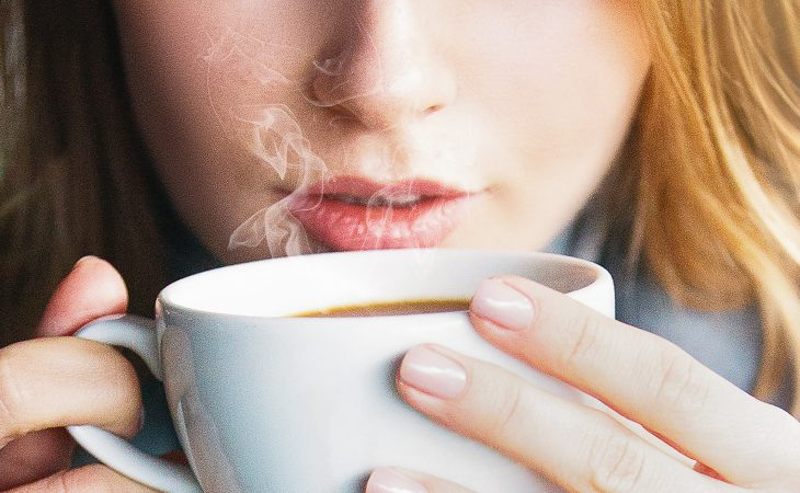 Woman holding cup of hot coffee to her nose and smelling it.