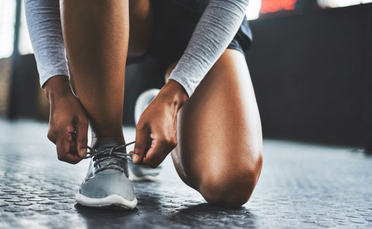 Athletic woman wearing workout gear kneeling on one knee, tying her shoes.