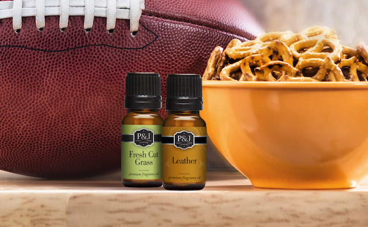 Leather and grass fragrance oils next to football and bowl of pretzels.
