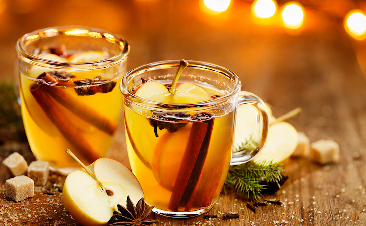 Glasses of apple cider with cinnamon sticks and orange slices in them.
