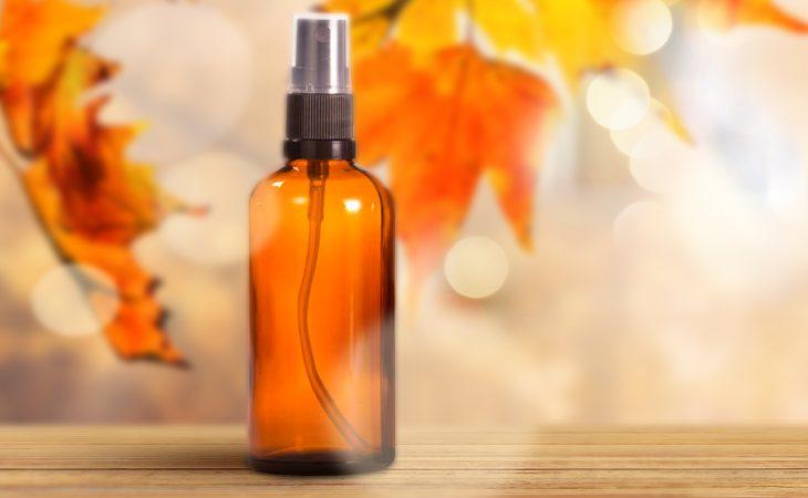 Dark glass fragrance oil linen spray bottle in front of colorful fall leaves.