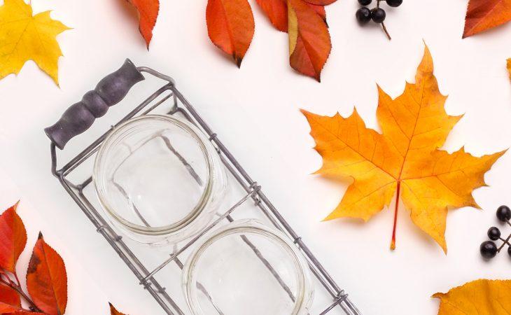Mason jars next to colorful fall leaves.