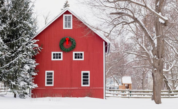 Classic red cabin in white snow with a large Christmas wreath on the side.