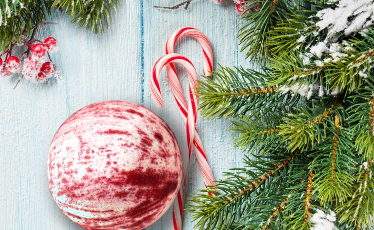 Photo of red and white bath bomb next to candy canes and Christmas tree leaves.