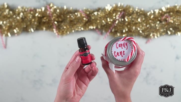 """Hands holding red """"candy cane"""" slime with a P&J Trading Candy Cane Fragrance Oil."""