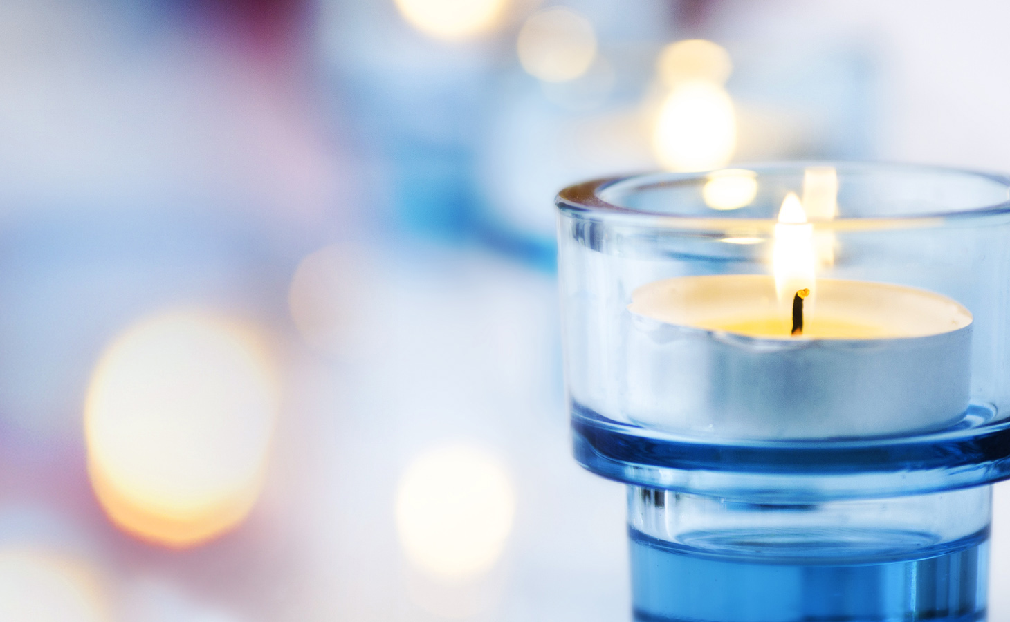 Small blue candle that is lit.