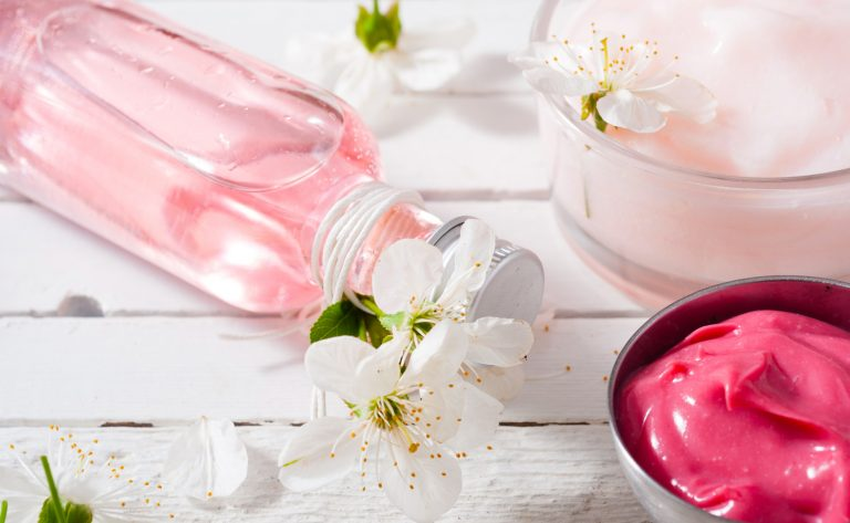 Pink perfume, lotions behind a white background with flowers.