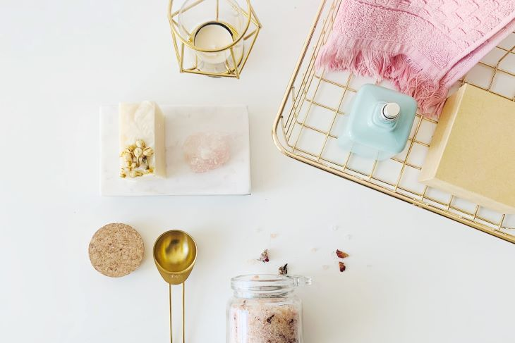 With a beautiful white background, opal soap, and pink wash cloth with gold finishes.