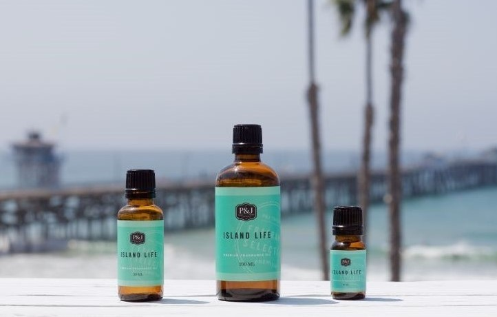 Three bright blue bottles of Island Life sitting on a white table, overlooking a brown pier with bright blue water underneath.