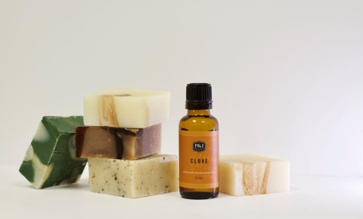 A brown, Clove scented fragrance oil bottle places near neutral tones of cold process soap.