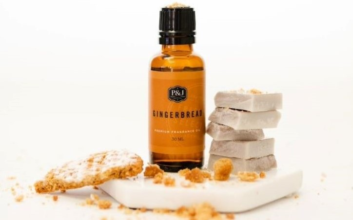 A P&J Trading Gingerbread Fragrance Oil with a brown label, sitting on a white background with gingerbread crumbs and wax melts next to it.