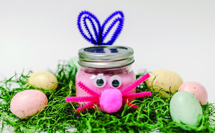 A mason jar with pink slime in it, dresses like an Easter bunny against green moss.