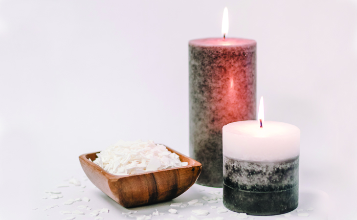Two lit dark candles with a brown bowl full of soy wax flakes against a white background.
