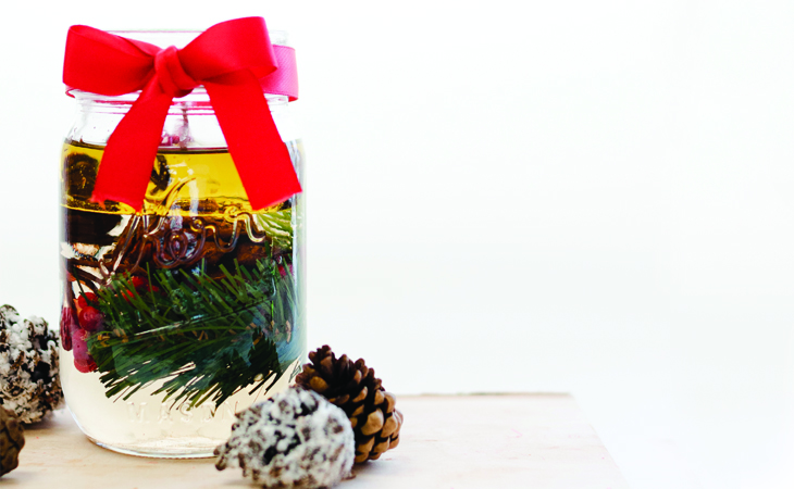 Christmas Wreath DIY oil candle against a white background with a red ribbon.