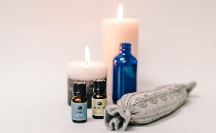 Two P&J Fragrance Oils with a grey heating pad, blue bottle bubble bath, white candles on a white background.
