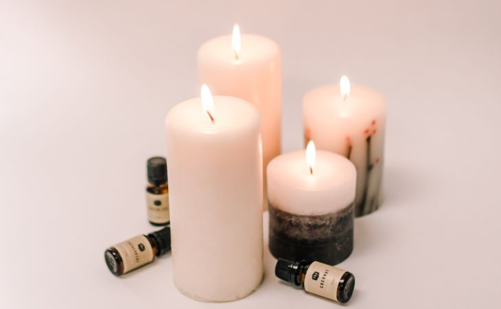 Lit white candles on a white background with P&J Trading fragrance oil bottles laying next to the candles.