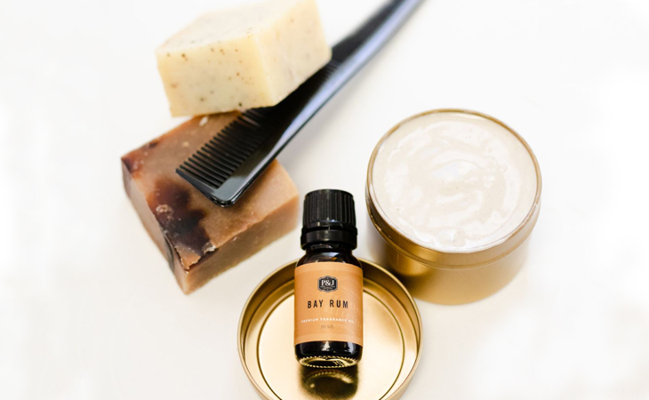 P&J Trading Fragrance Oil resting on a gold cap with homemade shaving cream in a gold container against a white background.