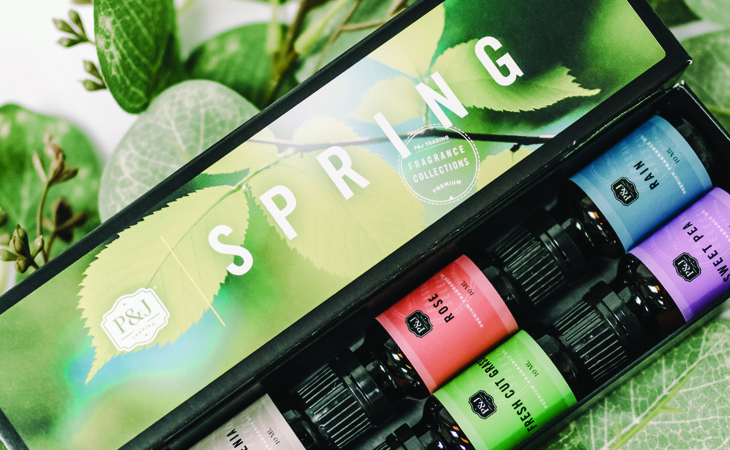 A green P&J Trading Spring Fragrance Oil Box with different, bright colored fragrances in the box against a bed of green leaves.