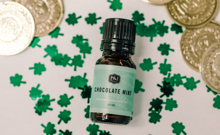 "A green ""Chocolate Mint"" P&J Trading fragrance oil bottle against a white background with little shamrocks all around it."