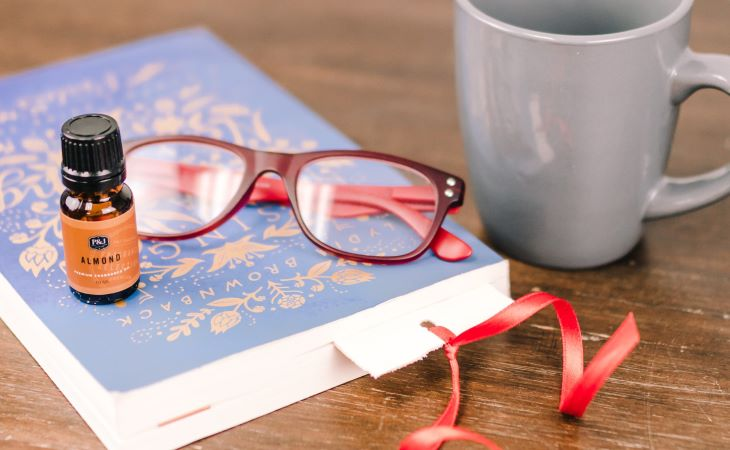 P&J Almond Fragrance Oil sitting on a blue book with red glasses and bookmark next to it on a brown background.