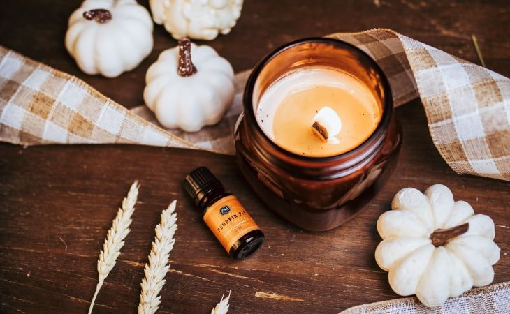 A P&J Pumpkin Pie Fragrance Oil bottle resting next to a candle in an amber bottle with white pumpkins and burlap.