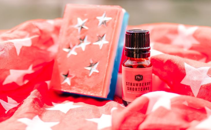 A red, white, and blue Fourth of July themed soap with silver stars next to a P&J Trading red, Strawberry Shortcake Fragrance Oil bottle.