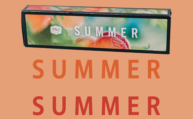"""P&J Summer Collection box with peaches on it resting on a peach colored background with the words """"summer""""."""