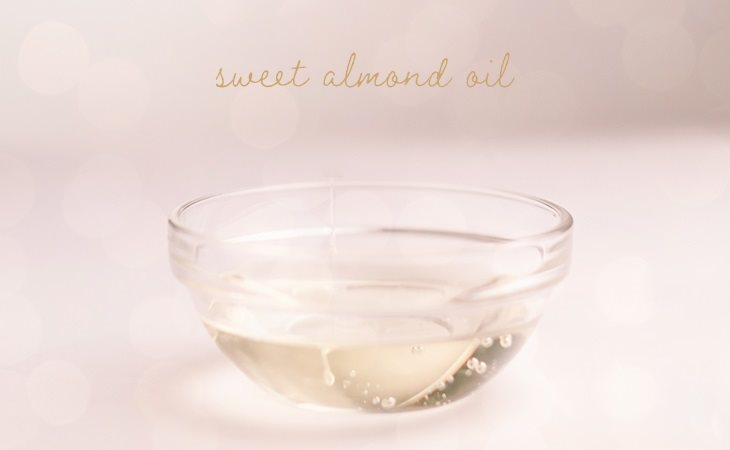 Small, clear bowl filled with sweet almond oil against a white background.